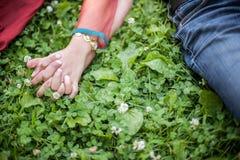 De handen van de paarholding op gras voor Liefdeconcept Royalty-vrije Stock Foto's