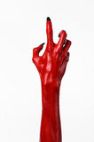 De handen van de rode Duivel met zwarte spijkers, rode handen van Satan, Halloween-thema, op een witte geïsoleerde achtergrond, royalty-vrije stock afbeeldingen