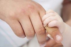 De handen van de vader en van de baby Stock Afbeeldingen
