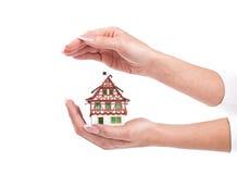 De handen van de vrouw beschermen weinig huis op wit royalty-vrije stock afbeeldingen