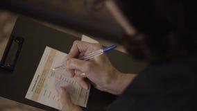 De handen van de vrouw houdt een zwarte omslag en vult een document op het stock video