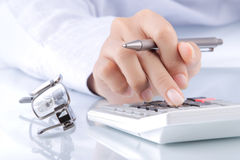 De handen van de vrouw met een calculator en een pen Royalty-vrije Stock Foto's