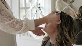 De handen van de vrouw met een kosmetische borstel passen make-up op het modelgezicht toe stock video