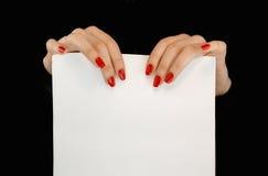 De handen van de vrouw met rode spijkers die een wit blad van document houden Stock Afbeeldingen