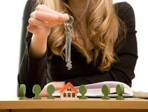 De handen van de vrouw met sleutel en stuk speelgoed huis Stock Foto's