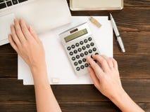 De handen van de vrouw op de calculator en laptop, pen, usb geheugenkaart Stock Foto's