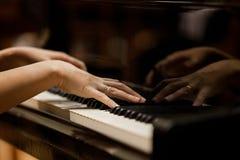 De handen van de vrouw op het toetsenbord van de piano Royalty-vrije Stock Foto's