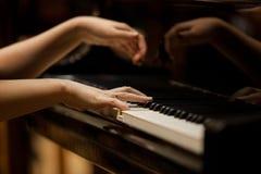 De handen van de vrouw op het toetsenbord van de pianoclose-up Royalty-vrije Stock Foto's