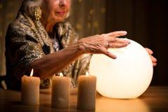De handen van de vrouw op kristallen bol royalty-vrije stock afbeelding