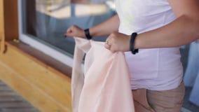 De handen van de vrouw van naden van lange lichtrose textiel in de zomerdag te scheuren stock footage
