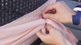 De handen van de vrouw verfraaien terug van stoel door lichtrose textiel met draad in de zomer stock video