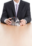De handen van de zakenman rond huis architecturaal model stock afbeeldingen