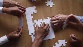 De handen van diverse commerciële teammensen werken samen assembleren raadsel samen stock footage