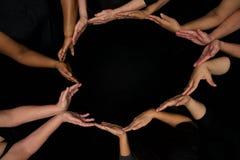 De handen van diversiteitsvrouwen die behulpzaam dient harten in werken stock afbeeldingen