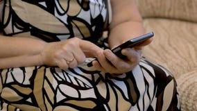 De handen van een bejaarde dat sms op een smartphone draait Close-up stock footage