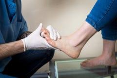 De handen van een jonge man artsenorthopedist leidt diagnostiek, de test van de voetvoet van een vrouw, voor de vervaardiging van royalty-vrije stock afbeeldingen