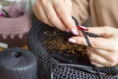 De handen van een jonge vrouw breien hoed van zwart synthetisch garen op een lichte houten oppervlakte Selectieve zachte nadruk royalty-vrije stock afbeelding
