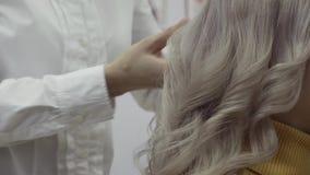 De handen van een kapper kammen een bundel van wit haar stock footage
