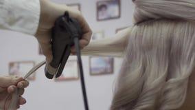 De handen van een kapper kammen een bundel van wit haar stock video
