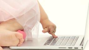 De handen van een klein meisje slaan de sleutels van laptop Witte achtergrond Sluit omhoog stock videobeelden
