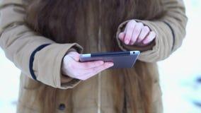 De handen van een meisje die met lang haar een tablet houden, herziet zij foto's stock footage