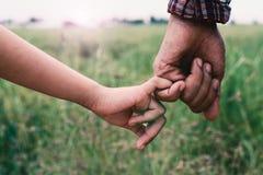 De handen van een meisjesholding met vader, Uitstekende filters Royalty-vrije Stock Foto's