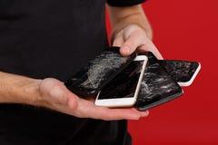 De handen van een mens die verscheidene gebroken houden smartphones Stock Foto's