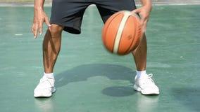 De handen van een mens kloppen basketbal op een groene achtergrond met kant 2 bij het BangYai-park, Nonthaburi in Thailand 2 juni stock video