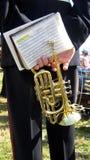 De handen van een musicus dragende trompet en een lied boeken in een gebeurtenis, overleg, of tonen Stock Fotografie