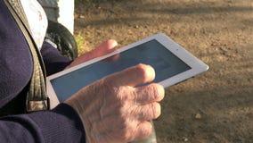 De handen van een oude vrouw glijden op het aanrakingsscherm uit van het nieuwe tabletwit stock footage