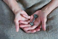 De handen van een oude vrouw houden de sleutel royalty-vrije stock fotografie