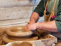 De handen van een Pottenbakker maken een grote pot stock afbeeldingen