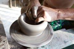 De handen van een pottenbakker vervaardigt kleipot stock foto