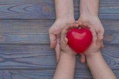 De handen van een volwassene en een kind worden gehouden in het rode hart, ziektekostenverzekering royalty-vrije stock foto's