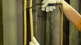 De handen van een vrouw de arbeider van de scène in handschoenen verwijdert het onderstel uit de kabel van het theatergordijn stock footage