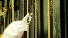 De handen van een vrouw het werk scène in handschoenen verwijderen de gehechtheid uit de kabel en verminderen het theatergordijn stock video