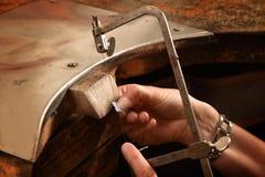 De handen van een vrouwelijke goudsmid werken aan een stuk van zilver met samengekomen stock fotografie