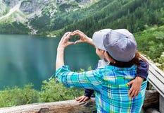 De handen van gelukkige moeder maken een hart voor haar zoon dichtbij als ondertekenen Royalty-vrije Stock Afbeeldingen