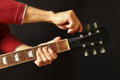 De handen van gitarist stemt de gitaar op donkere achtergrond stock fotografie