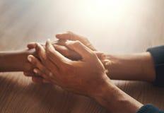 De handen van de de handholding van het paar op houten bureau stock afbeelding