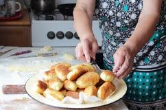 De handen van het bejaarde zetten een klaar pastei op een schotel stock afbeeldingen