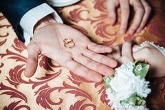 De handen van het huwelijkspaar op de lijst en de ringen royalty-vrije stock foto