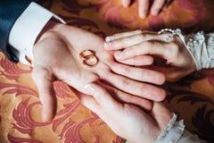 De handen van het huwelijkspaar op de lijst en de ringen royalty-vrije stock afbeelding
