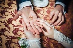 De handen van het huwelijkspaar op de lijst en de ringen stock fotografie