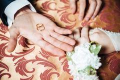 De handen van het huwelijkspaar op de lijst en de ringen stock foto's
