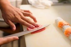 De handen van het Japanse de chef-kok` s mes van de sushisashimi stock afbeelding