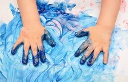 De handen van het kind die in blauwe verf worden geschilderd royalty-vrije stock afbeelding
