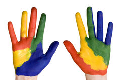 De handen van het kind die in kleurrijke verven worden geschilderd. Stock Afbeeldingen