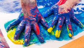 De handen van het kind die in kleurrijke verven worden geschilderd Onderwijs, school, creativiteit en het schilderen concept royalty-vrije stock foto