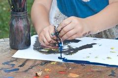 De handen van het kind het schilderen Stock Foto